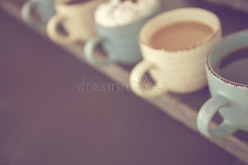 abstracte achtergrond blur Rij van koffiekoppen met verse koffie op een houten lijst Negatieve ruimte voor tekst stock afbeelding