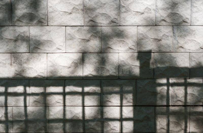 Abstracte achtergrond van geweven steenmuur met schaduwen van bomen en omheining op het royalty-vrije stock foto
