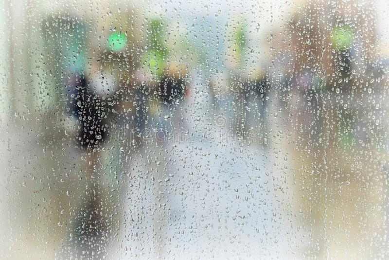 Abstracte achtergrond van mensen die zich onderaan de stadsstraat haasten in regenachtige dag Opzettelijk motieonduidelijk beeld  royalty-vrije stock foto