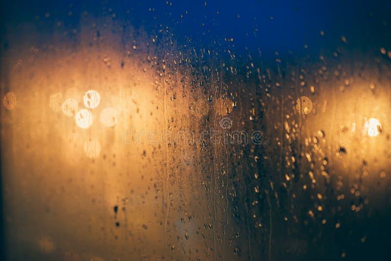Abstracte achtergrond van vage lichten door vochtig venster met stock foto's