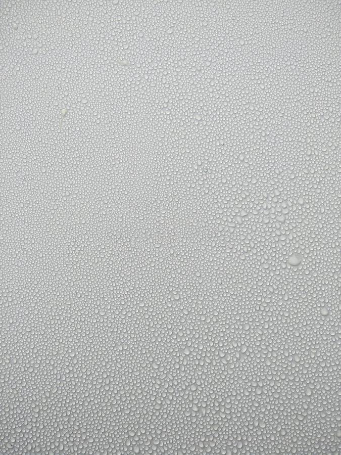 Abstracte achtergrondwaterdalingen op glas, regendruppels op vensterglas, dauw en vochtigheid met natte vloer stock foto