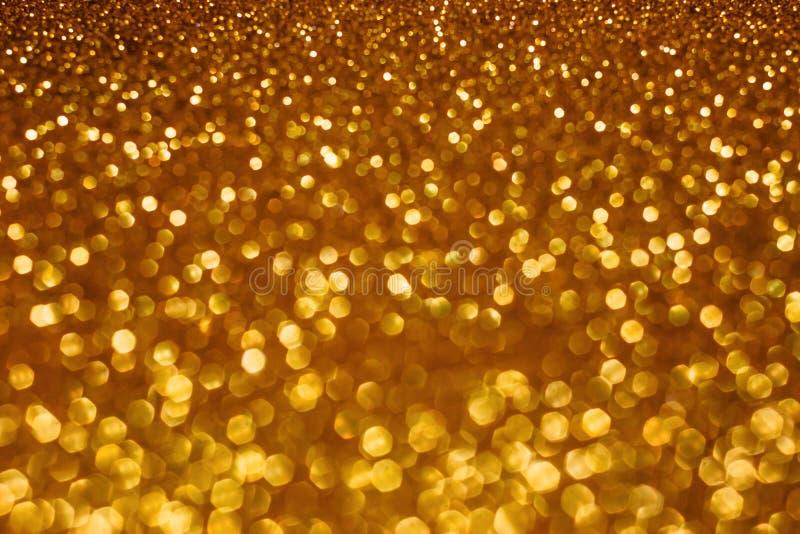 Abstracte bokehachtergrond van de Kerstmisvakantie met gouden lichten Schitter gouden bokehachtergrond royalty-vrije stock afbeeldingen
