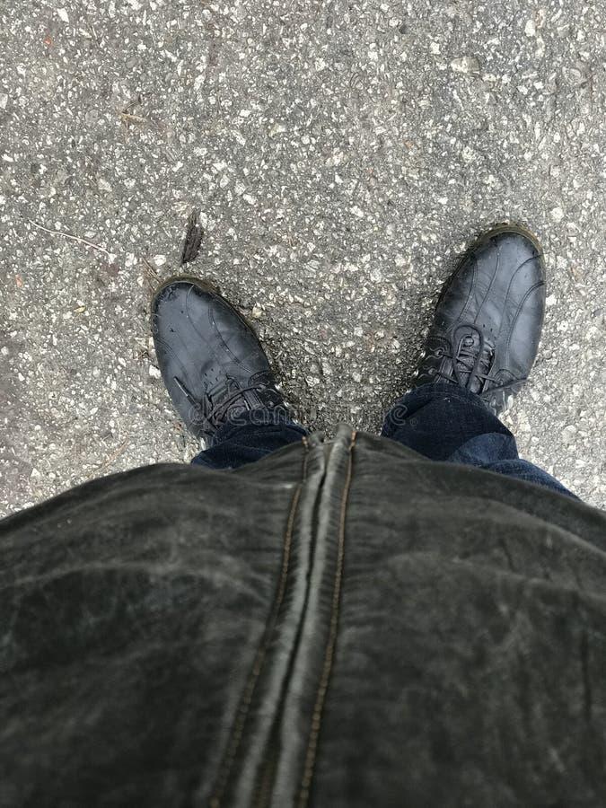 Abstracte close-upmening van de helft van het persoonslichaam van omhoog onderaan status op grijze asfaltoppervlakte, grond royalty-vrije stock afbeeldingen