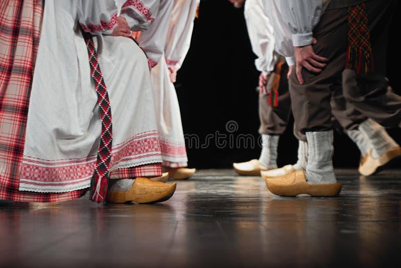 Abstracte compositie met poten gekleed in de Litouwse traditionele clothe die danst in folklore stock fotografie