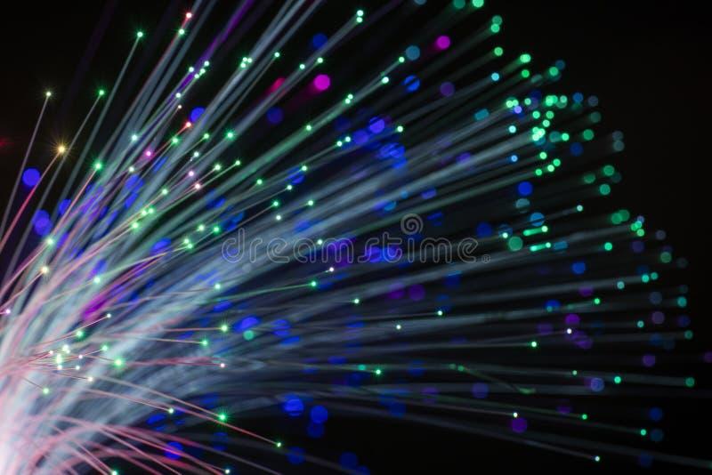 Abstracte conceptuele foto van vezeldraden die met veelkleurig licht gloeien Zwarte achtergrond royalty-vrije stock foto