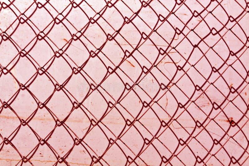 abstracte de omheiningstextuur van de kettingsverbinding tegen grungy kleurenmuur stock afbeelding