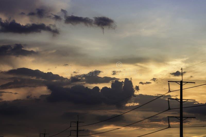 Abstracte de zonsonderganghemel van het textuurpatroon en wolken natuurlijk heldere kleuren, met hoogspanningspool, voor decorati stock foto's