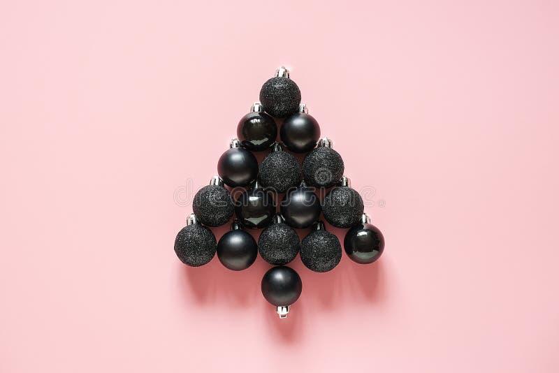 Abstracte die Kerstboom van de zwarte decoratie van snuisterijballen op roze achtergrond wordt gemaakt De minimale stijl Creatiev stock foto