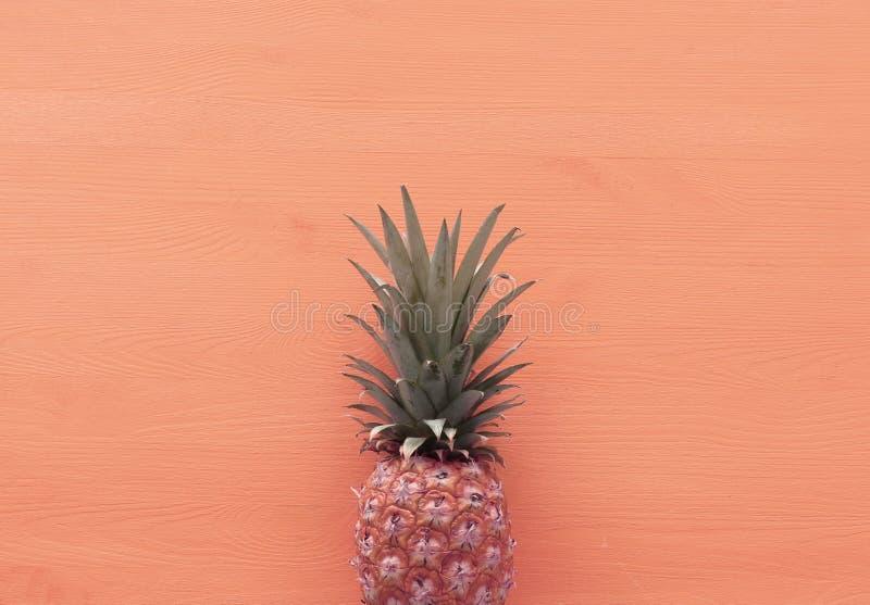 Abstracte foto van ananas over roze houten achtergrond Strand en tropisch thema Hoogste mening royalty-vrije stock afbeelding