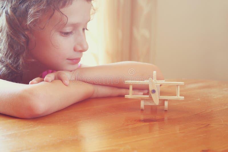 Abstracte foto van leuk jong geitje die oud houten vliegtuig bekijken Selectieve nadruk inspiratie en kinderjarenconcept royalty-vrije stock afbeeldingen