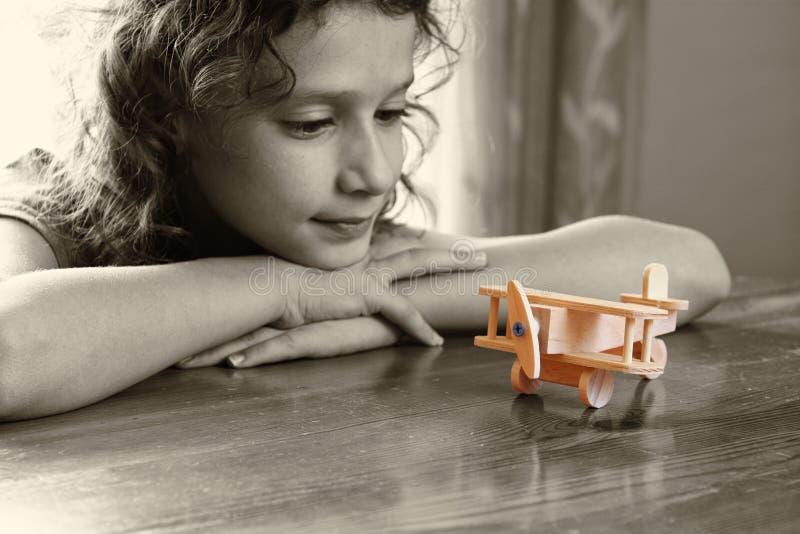 Abstracte foto van leuk jong geitje die oud houten vliegtuig bekijken Selectieve nadruk inspiratie en kinderjarenconcept stock fotografie