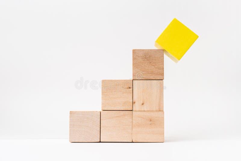 Abstracte geometrische echte houten kubuspiramide op witte vloerachtergrond Het ` s het symbool van maakt een fout, loopt in een  stock foto