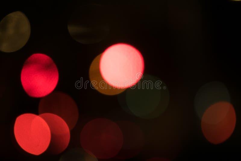 Abstracte multi-colored bokehballen die over een donkere achtergrond drijven stock afbeelding