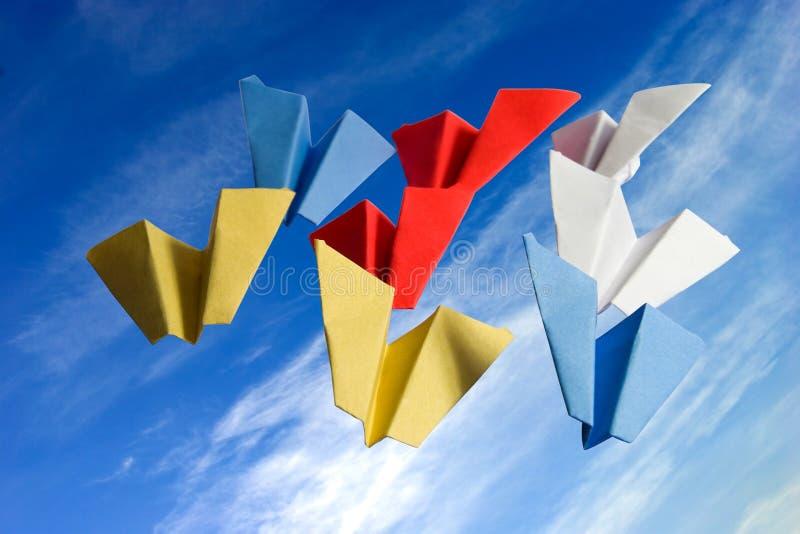 Abstracte origamedocument vliegtuigen op bewolkte hemelachtergrond stock afbeeldingen