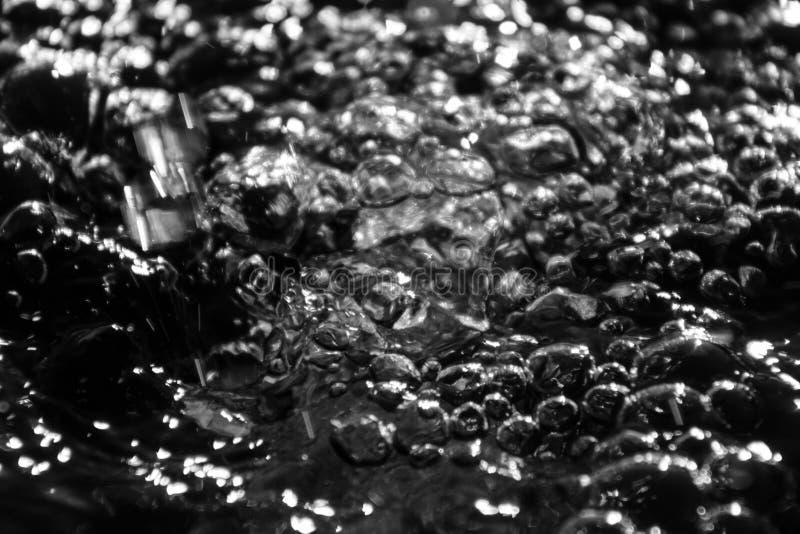 Abstracte plonsen van water op een zwarte achtergrond royalty-vrije stock fotografie