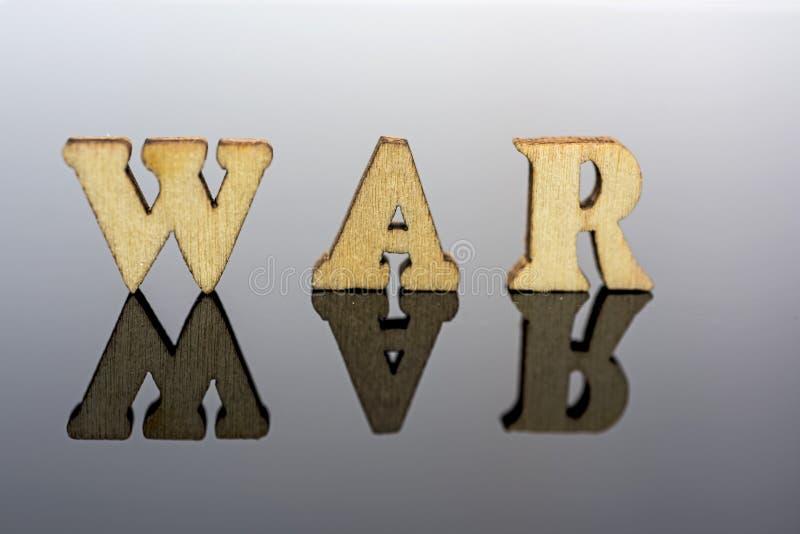 Abstracte samenstelling van oorlog Geïsoleerde houten brieven en rode glasbal stock fotografie