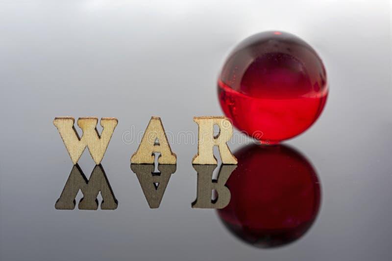 Abstracte samenstelling van oorlog Geïsoleerde houten brieven en rode glasbal stock afbeeldingen