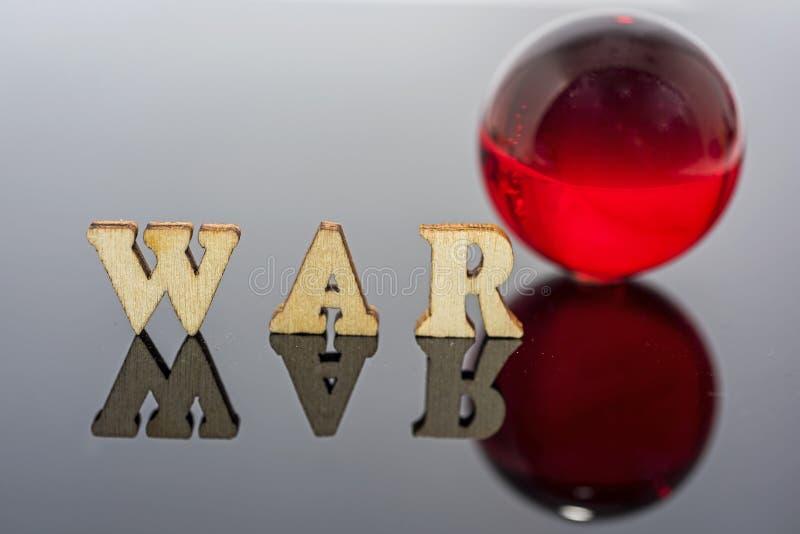 Abstracte samenstelling van oorlog Geïsoleerde houten brieven en rode glasbal stock foto