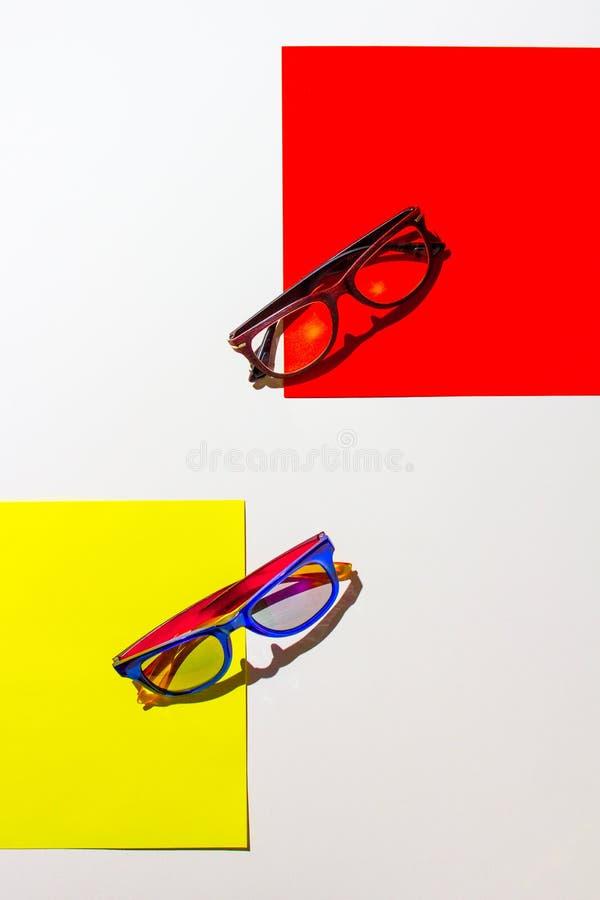 Abstracte samenstelling van zonnebril op kleurrijke cardboards en de witte achtergrond stock afbeelding