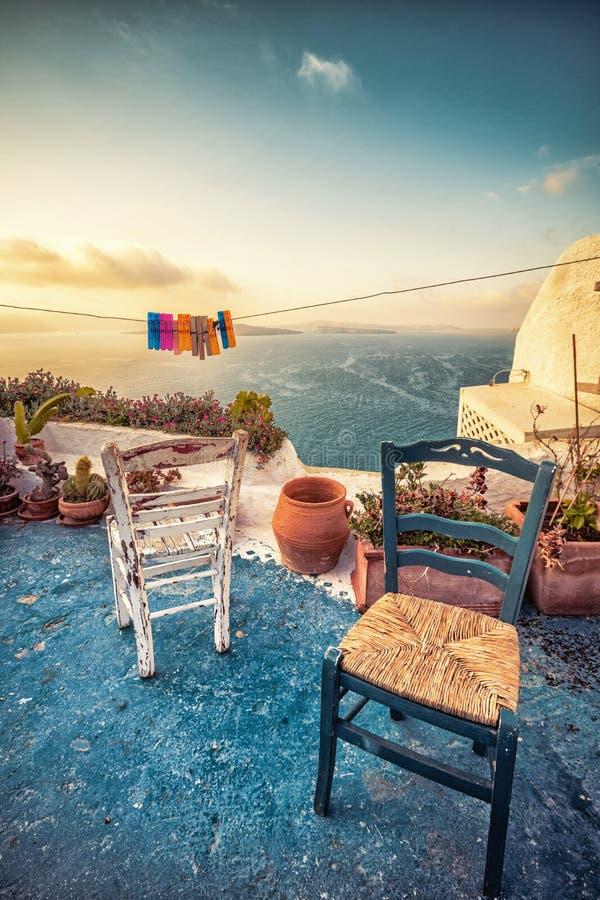 Abstracte scène van twee houten stoelen op een terras op Santorini stock foto