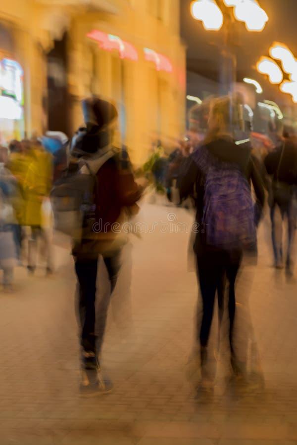Abstracte uitstekende toonmotie Onduidelijk beeldbeeld van Straat, meisje en kerel met rugzakken, heldere stadslichten met bokeh stock afbeelding