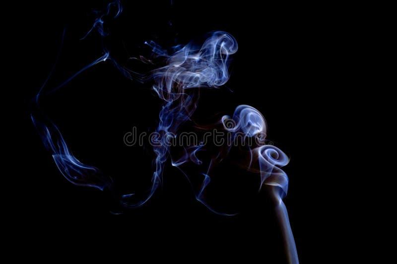 Abstracte violette blauwe grijze rookranken in lucht op zwarte backgro stock afbeelding