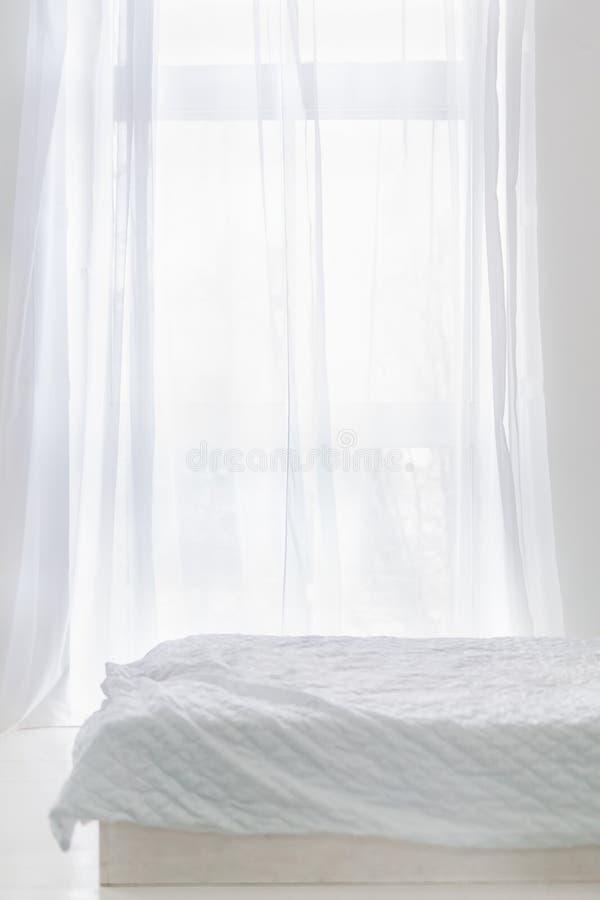 Abstracte witte ruimte met bed en venster met wit gordijn stock foto's