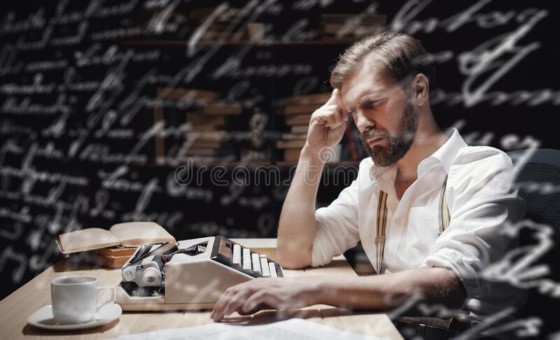 Abstracted author at workplace. Abstracted author sitting at typewriter in dark interior with bookshelf background stock photo