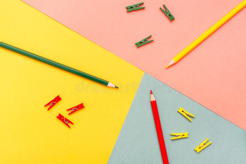 Abstracted are colored pencils and clips on yellow, green, red. Abstracted are colored pencils and clips on yellow, green and red backgrounds. Top View stock images