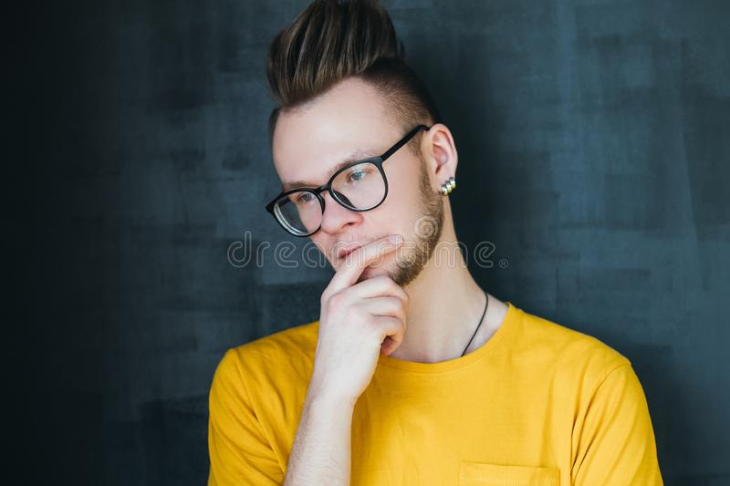 Abstracted disturbed emotion hipster guy portrait. Portrait of abstracted hipster guy with comb over haircut. Young emotional man ing chin. Disturbed facial royalty free stock photo