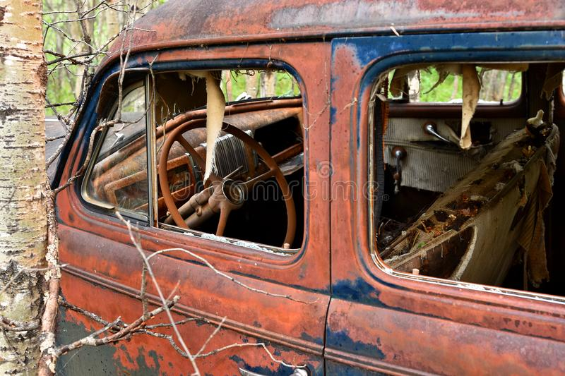 Old Rusted Car Wreckage. An abstracted image of the rusted wreckage of an old abandoned car stock photo