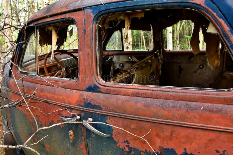 Old Rusted Car Wreckage. An abstracted image of the rusted wreckage of an old abandoned car stock image
