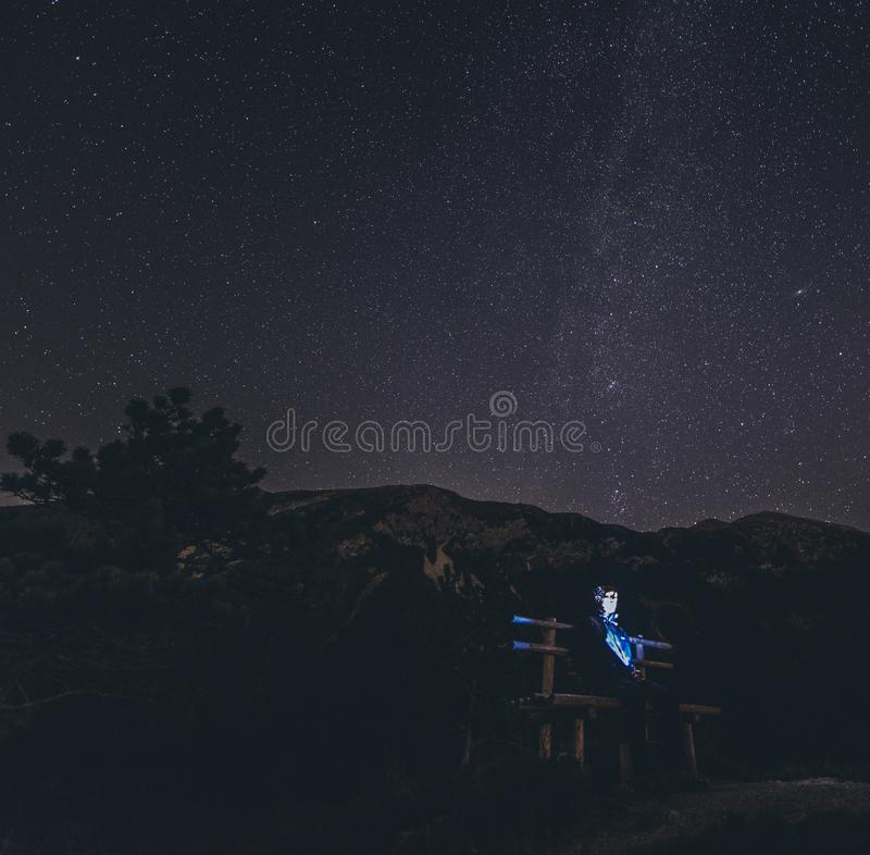 Abstracted man sitting on a bench under a beautiful sky full of stars. An abstracted man sitting on a bench under a beautiful sky full of shining stars stock images