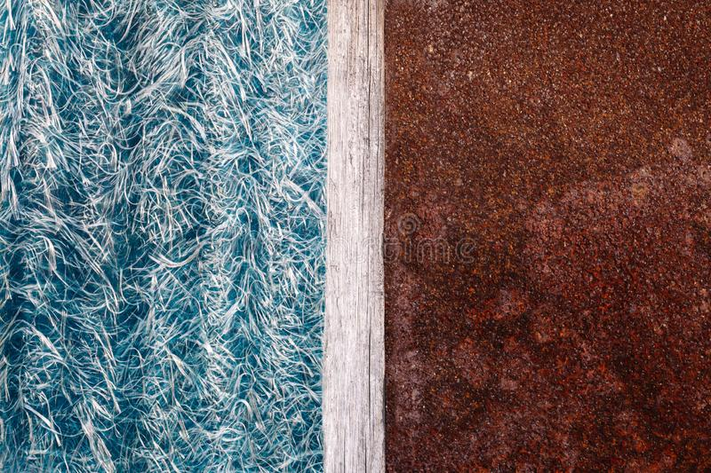 Abstraction of blue textolite slate, background in half with a rusty metal plate and a dividing strip of wood royalty free stock photo