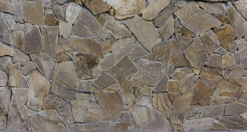 Abstraction from stones. Embedded stone wall of different shapes royalty free stock photography
