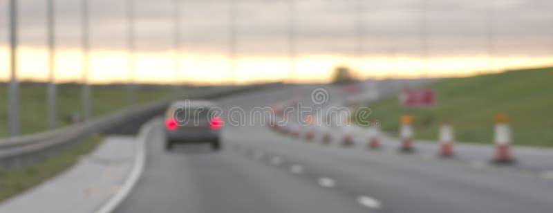 Abstraia o carro borrado na estrada no por do sol, Inglaterra imagem de stock