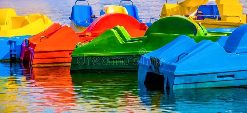 Abstraia o tiro colorido de barcos do pedal com reflexões na água fotografia de stock