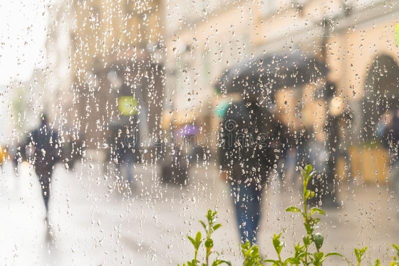 Abstraia a silhueta borrada dos homens sob o guarda-chuva, rua da cidade vista através dos pingos de chuva no vidro de janela, bo fotos de stock royalty free