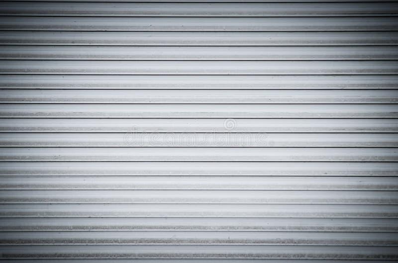 Abstrakcjonistycznej białej rolki kruszcowe żaluzje drzwiowe z horyzontalnymi liniami Tło obrazy royalty free