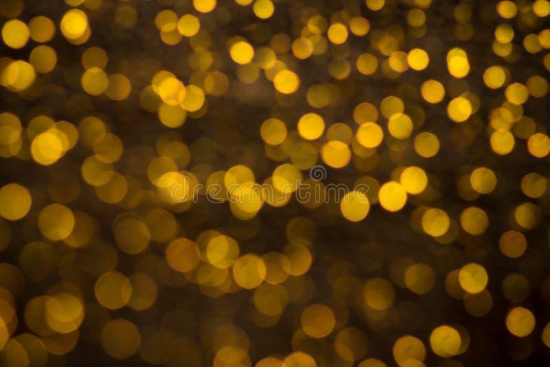 Abstrakcjonistyczny backgroung złoty błyskotliwości i łuny bokeh miękki jaśnienie zaświeca Marzycielski błyskotania tło zdjęcia stock