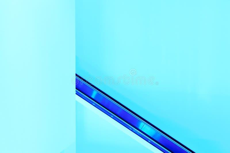 Abstrakcjonistyczny geometrical tło z bocznym widokiem eskalator i ściany zaświecamy malujemy w jaskrawym błękicie Abstrakcjonist fotografia royalty free