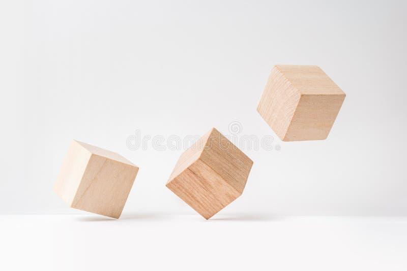 Abstrakcjonistyczny geometryczny istny drewniany sześcian z surrealistycznym układem na białym podłogowym tle symbol przywódctwo, zdjęcia stock