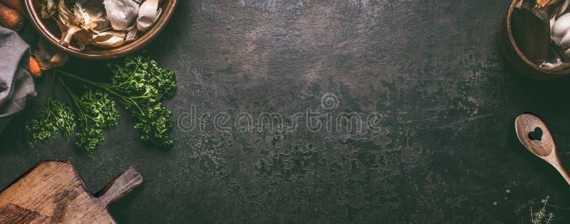 Abstrakcjonistyczny karmowy tło Odgórny widok ciemny nieociosany kuchenny stół z drewnianą tnącą deską i kulinarną łyżką, rama Sz obrazy stock