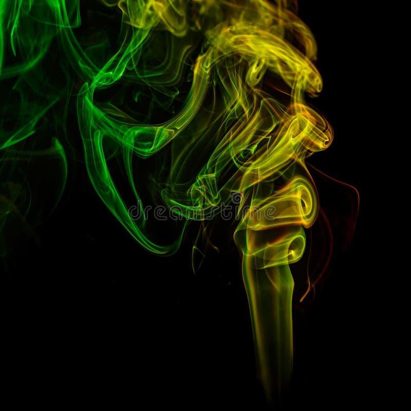 Abstrakcjonistyczny kolor żółty i zieleń dymimy od aromatycznych kijów zdjęcie stock