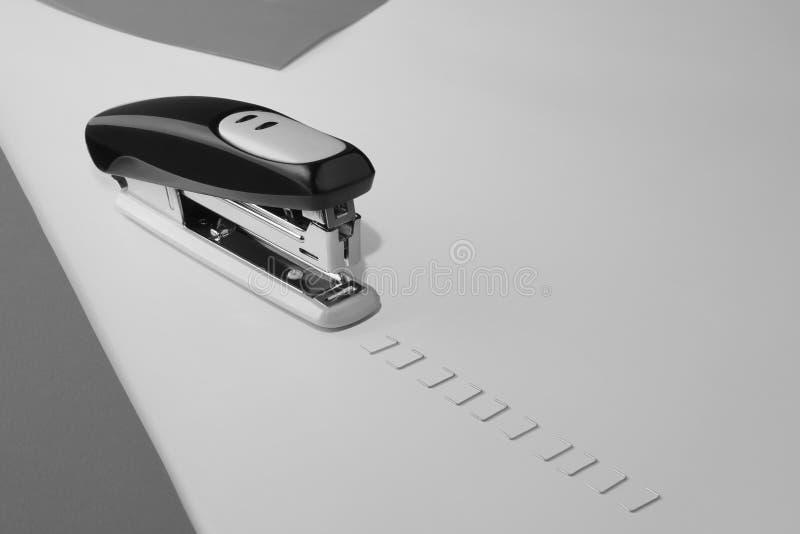 Abstrakcjonistyczny skład z biurowym zszywaczem i zszywki jako tory szynowi zdjęcia stock