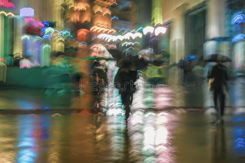 Abstrakcjonistyczny tło zamazani ludzie pod parasolami śpieszy w dół miasto ulicę w dżdżystym wieczór, impresjonizm fotografia stock