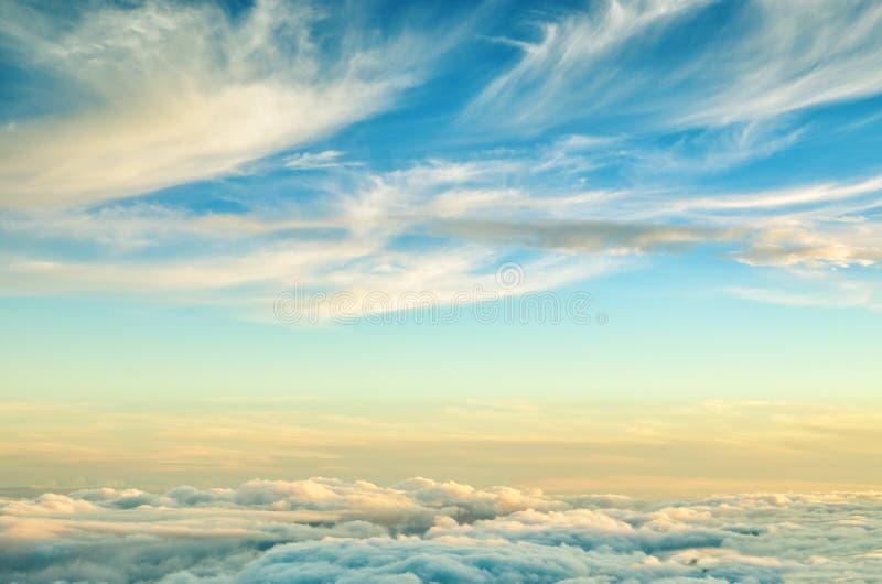 Abstrakcjonistyczny tło z złota i błękita kolorami chmurnieje Zmierzchu niebo nad chmury obrazy stock