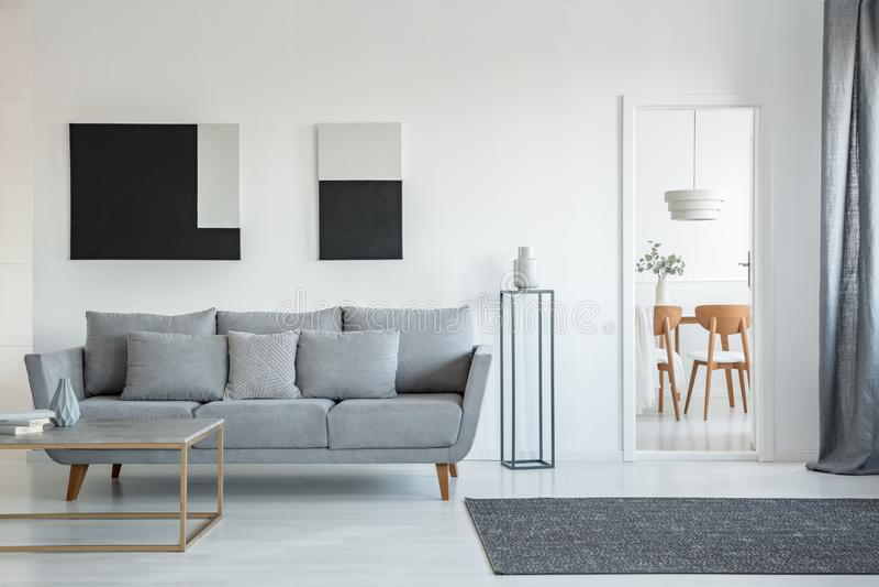 Abstrakcyjne malowanie czarno-białe na pustej ścianie stylowego wnętrza salonu z wygodną szarą kanapą z poduszkami obrazy royalty free