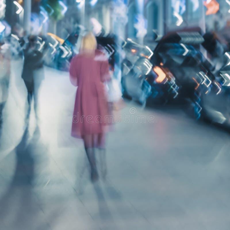Abstrakcyjne tło ulicy miejskiej wieczorem, sylwetka blond dziewczyny z powrotem do nas, zamazany ruch Sezony obrazy stock