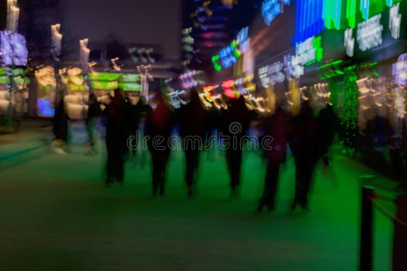 abstrakcyjny tło Intencjonalna ruch plama Grupa młodzi ludzie iść wzdłuż ulicy Zielony sklepowy okno obraz stock